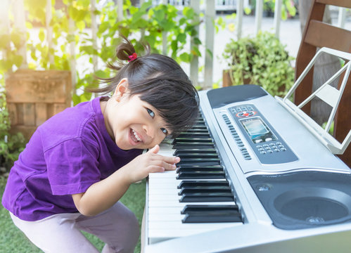 Little toddler girl smile having fun during learning to play musical electronic keyboard synthesizer at music home academy