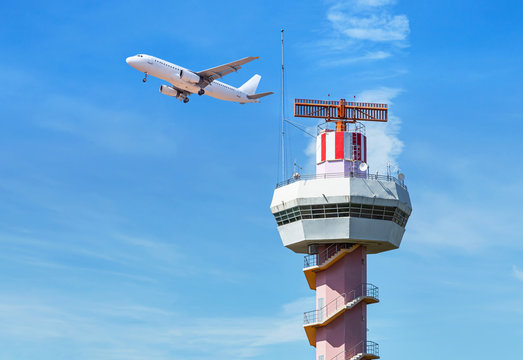 Radar  air traffic control tower in international airport while airplane taking off under blue sky.