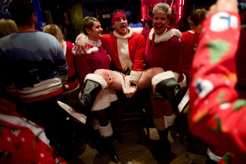 """Kyle Rannels pulls down his Santa Claus outfit while being lifted for a photo at The Field House party after the """"Running of the Santas"""" annual pub crawl never materialized in Philadelphia"""