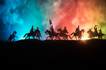 Medieval battle scene with cavalry and infantry. Silhouettes of figures as separate objects, fight between warriors on dark toned foggy background. Night scene. Fototapete