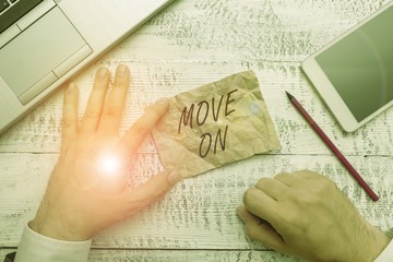 Writing note showing Move On. Business concept for to leave the place where you are staying and go somewhere else Hand hold note paper near writing equipment and smartphone