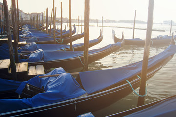 Türaufkleber Gondeln Vintage gondolas in Venice covered with blue material at dawn