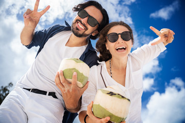 Beautiful young couple on a background of blue sky and clouds with coconuts in their hands. Joyful smiles and laughter. Honeymoon travel and vacation on the tropical ocean, picture from below