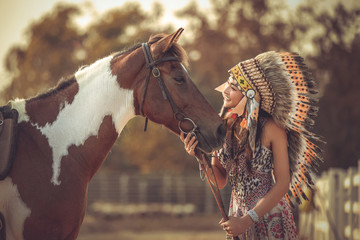 A woman wearing a bohemian dress , on her head wearing an apache feather hat , she standing with horses in a horse farm and soft sunshine.