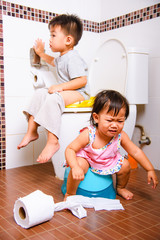 Asian Two brothers little  kid and baby sitting on a kid bathroom accessory toilet