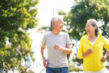 happy chinese senior couple running outdoors