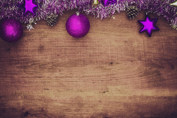Purple christmas decorations on wooden background. Flat lay with copy space.