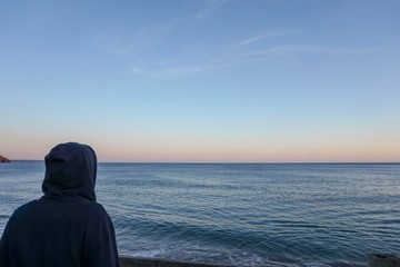 A male surfer wears a hoodie to warm up as he looks at the calm ocean. The skies are a dusty orange colour and the water is flat