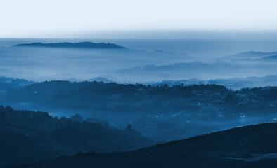 Foto auf Acrylglas Blau Jeans Layers of foggy mountains blue toned