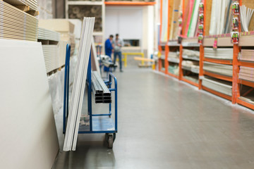 Trolley in a hardware store loaded with construction materials. Repair and construction concept
