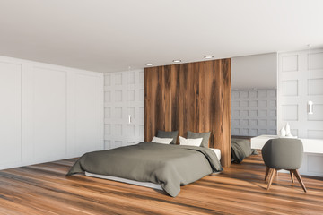 White and wooden bedroom corner with armchair