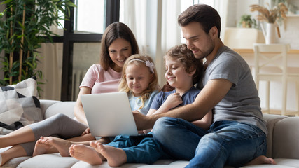 Married couple and kids using laptop having fun in internet