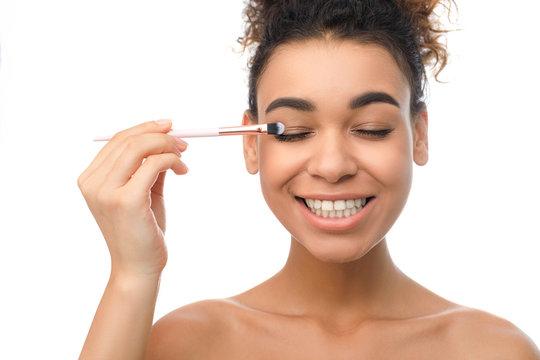Happy black woman applying eyeshadows with brush