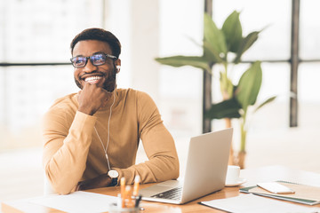 Smiling black worker in glasses listening to music