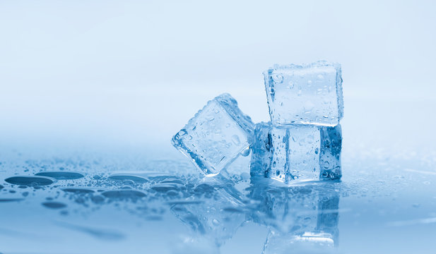 Ice cubes square with drops water clean on blue background