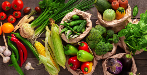 Healthy background with fresh different vegetables in reusable paper bags