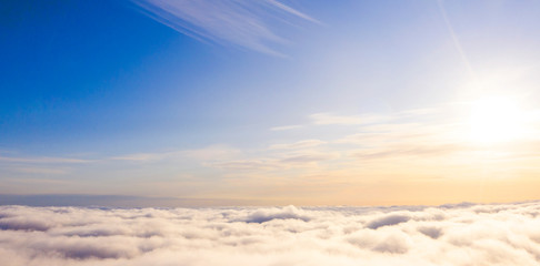 Aerial view White clouds in blue sky. Top view. View from drone. Aerial bird's eye view. Aerial top view cloudscape. Texture of clouds. View from above. Sunrise or sunset over clouds