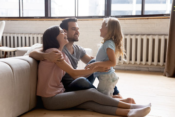 Family sit on warm floor enjoy communication spend time indoors