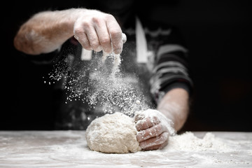 Stores photo Pizzeria White flour flies in air on black background, pastry chef claps hands and prepares yeast dough for pizza pasta