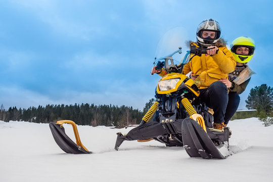 Riding a snowmobile. Two people ride a snowmobile. Pair races on snowmobiles. Extreme sports. Riding through snowdrifts. Winter sports. Man and a woman are resting together. Car for moving in snow.