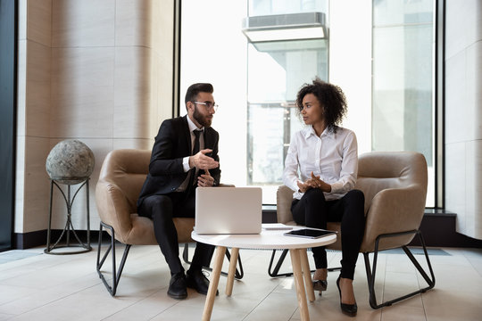 Multiracial business partners cooperate work on laptop together