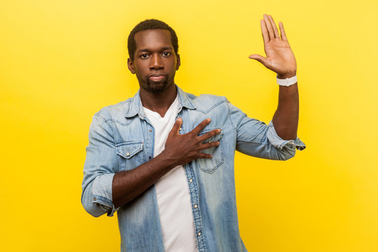 I swear! Portrait of honest serious man in denim casual shirt with rolled up sleeves keeping hand on chest and raising palm, giving promise, pledge. indoor studio shot isolated on yellow background