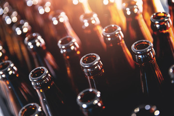 Closeup open brown glass dark bottles for beer alcohol, lens flare