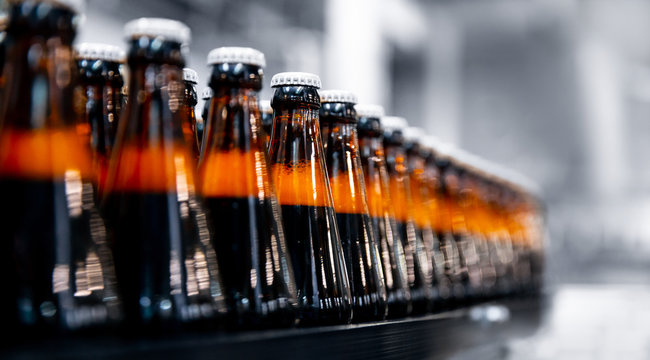 Glass bottles of beer on dark background with sun light. Concept brewery plant production line