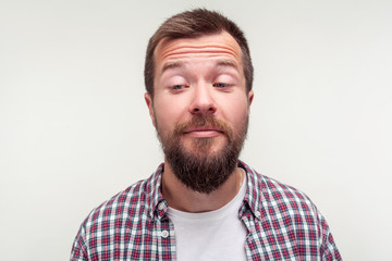 Portrait of funny awkward bearded man in casual plaid shirt standing with crossed eyes, comic silly expression, looking carefree and dumb, making faces. studio shot isolated on white background
