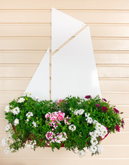Summer Flowers in a Sailing Boat hanging on Wood Panel Wall