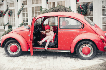 Türaufkleber Autos aus Kuba Smiling cute winter girl in red hat sitting in car having fun medium shot. Happy beautiful female baby in warm clothing having positive emotion outdoor surrounded by snowflakes enjoying childhood