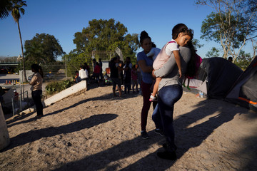 An asylum seeker carries her daughter in an encampment where they live in Matamoros