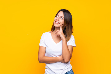 Young woman over isolated yellow background thinking an idea while looking up Fotomurales