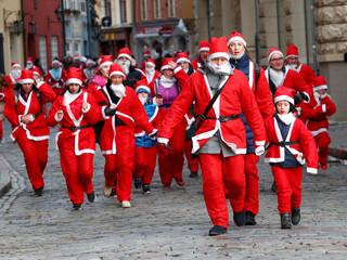 People dressed as Santa Claus take part in the charity Santa Fun Run in Riga