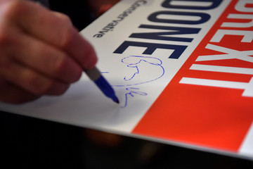 Britain's Prime Minister Boris Johnson signs a placard at the Conservative Campaign Headquarters Call Centre in central London