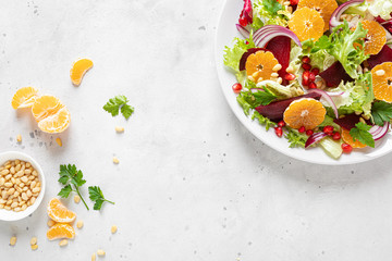 Christmas salad with boiled beet, red onion, tangerines, pomegranate, parsley, pine nuts and...