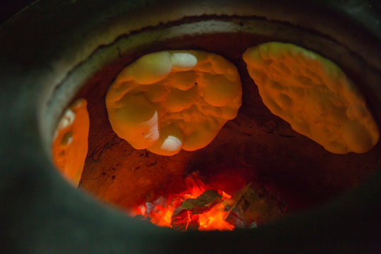Naan Bread and flame on the hot oven