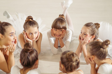 charming pretty little girls ballerinas lying on floor in circle, have a rest after performing ballet dance in studio