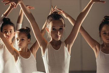 graceful flexible kid girl ballerina performing classic ballet while her friends dancers stand in ballet pose behind her, in the background