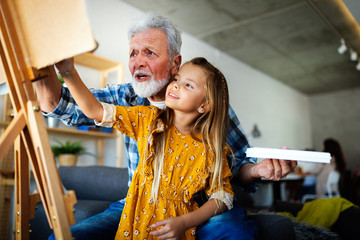 Senior man, grandfather and his grandchild drawing, painting together. Happy family time