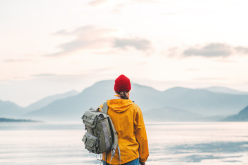 Back view of male tourist with rucksack standing on coast in front of great mountain while journey.  Man traveler wearing yellow jacket with backpack explore scandinavia nature. Wanderlust outdoor