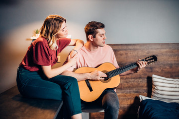 Canvas Prints Bar lovely couple playing the guitar at home together, love. leisure time