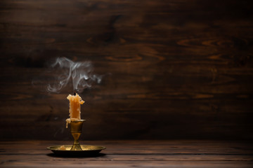 extinct old candle with vintage brass candlestick on wooden background in minimalist room interior with copy space