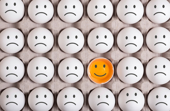 different egg stands out from the crowd and smiling.turn the disadvantage into an advantage