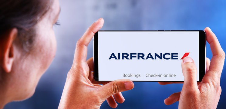 Woman holding smartphone displaying logo of Air France