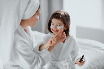 beauty procedures at home. small daughter and her mother use patches under eye, wearing bathrobe...