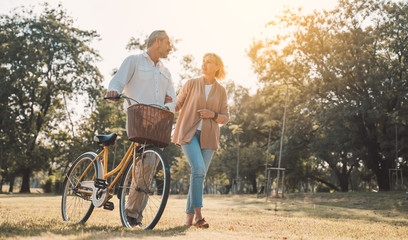 Beautiful Senior couple walking their bike along happily talking in park.mature couple in summer park.Elderly man and old woman with bicycles outside in spring nature.