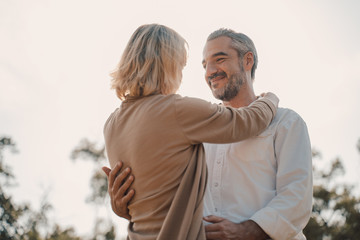 Older Lover and dating concept.Beautiful Senior couple romantic dancing in park.mature couple in summer park.Elderly man and old woman in love dancing outdoors.