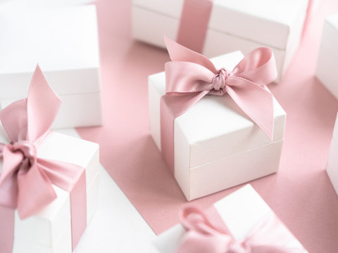 Gift boxes wiyh powdery ribbon. Powdery background. Silver bracelet with charms. Gift box for the New Year and Christmas. Best gift for Valentines Day and Mothers day.