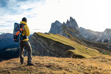Young man hiking at Seceda mountain peak at sunrise. Backpack, yellow jacket, boots, beanie. Traveling to puez Odle, Dolomites, Trentino, Italy. Wall mural